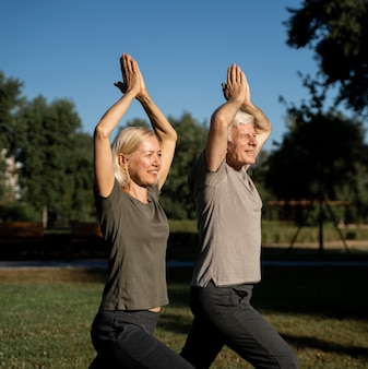 Side view of elderly couple doing yoga outside