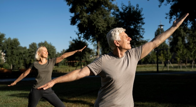 Side view of elderly couple practicing yoga outdoors