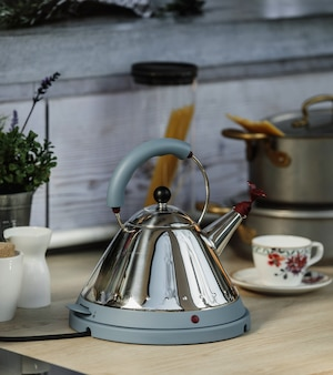 Side view of electric modern kettle with whistle on a wooden table in kitchen