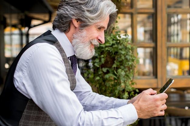 Maschio elegante di vista laterale con la barba che passa in rassegna il telefono cellulare