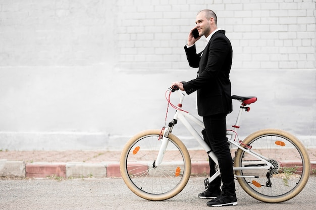 Side view elegant male with bicycle outdoors