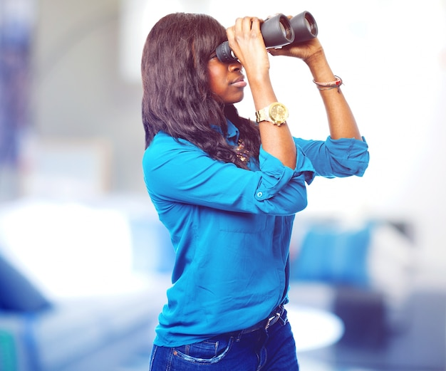 Side view of elegant young woman with binoculars