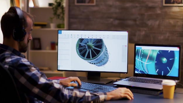 Side view of engineer wearing headphones and working on a turbine using modern software for design.