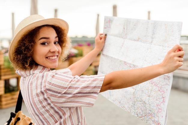 Женщина-энтузиаст, путешествующая одна с картой, вид сбоку