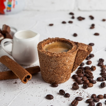 Side view espresso in a cork cup with carafe with milk, cinnamon, coffee grains