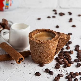 牛乳、シナモン、コーヒーの穀物とデカンタとコルクカップのエスプレッソの側面図