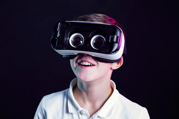 Side view of excited kid in white t-shirt and virtual reality headset standing bending forward playing with joystick on black