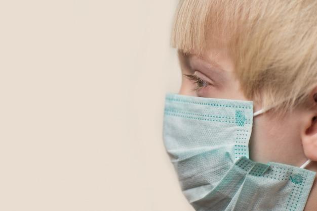 医療マスクの子供の側面図。ウイルスからの子供の保護。