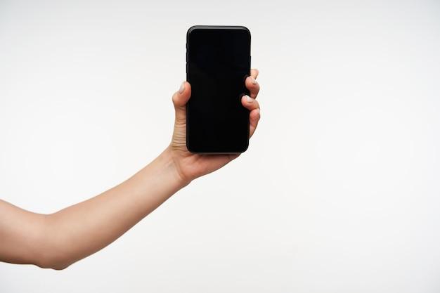 Vista laterale della mano della giovane femmina dalla carnagione chiara che viene sollevata mantenendo il telefono cellulare nero e mostrando lo schermo, isolato su bianco