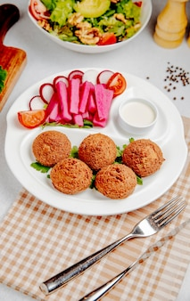 Side view of falafel with fresh vegetables