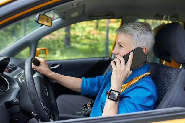 Side view of fashionable mature careless european female with blonde pixie hair sitting in driver's seat with one hand on steering wheel, holding cell phone, talking, concentrating on road