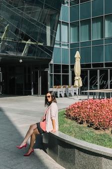 Vista laterale di una donna alla moda che si siede fuori dell'edificio per uffici