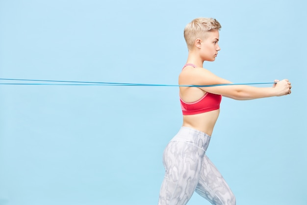 Side view of fashionable young caucasian female with sporty fit body and pixie hairstyle pulling strap with hands in front of her. pretty girl in trendy sportswear training, using resistance band