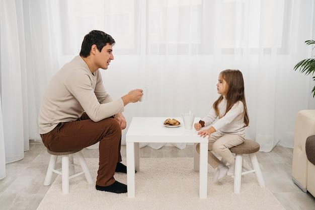 Vista laterale di padre e figlia che mangiano insieme a casa
