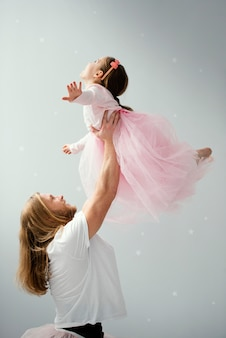 Side view of father and daughter in tutu skirts dancing