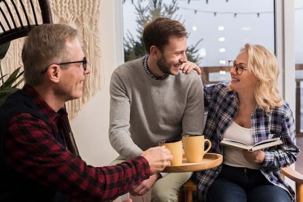 Side view of father giving mother and son warm cup