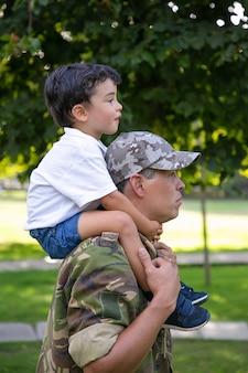 Vista laterale del padre che tiene il figlio sul collo e cammina nel parco cittadino. figlio caucasico seduto sul collo di papà in uniforme militare, abbracciandolo e guardando avanti. paternità e concetto di ritorno a casa