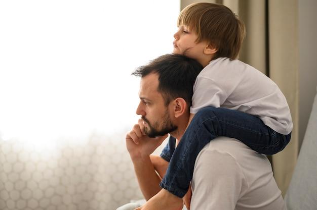 Вид сбоку отец держит сына