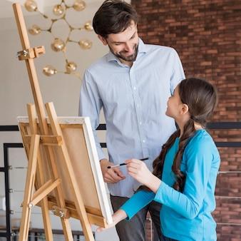 Вид сбоку отец учит девочку рисовать