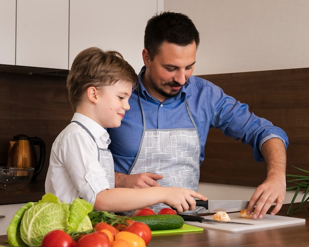 Side view father teaching son to cut vegetables