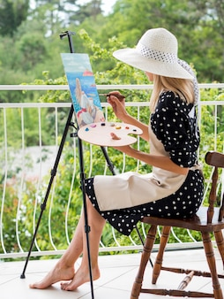 Side view of female artist painting outdoors