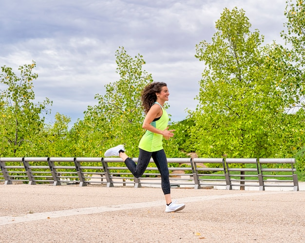 Side view of a female athlete smiling while practicing run in the park. she is brunette and her hair is moving
