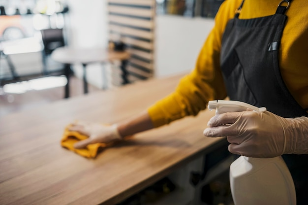 Side view of female barista cleaning table while wearing latex gloves