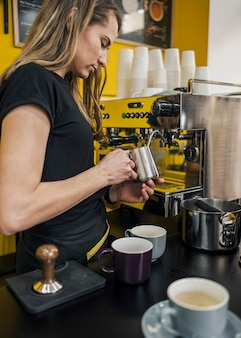 Side view of female barista frothing milk
