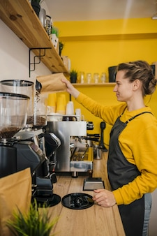 Side view of female barista grinding coffee