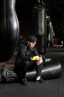 Side view of female boxer holding flask next to punching bags
