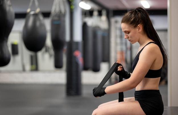 Vista laterale del pugile femminile che prepara per l'addestramento