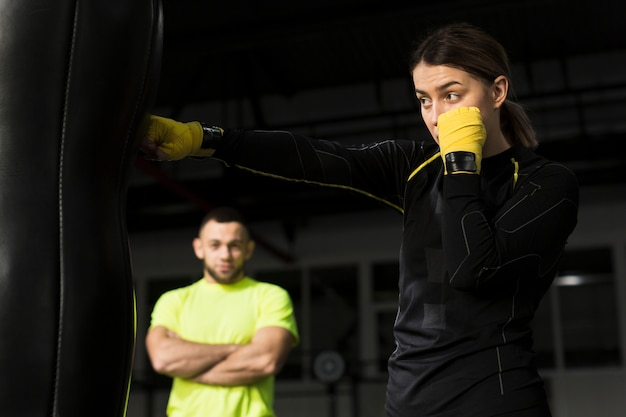 Side view of female boxer with protective gloves punching heavy bag