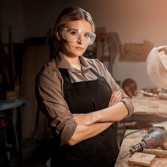 Vista laterale del falegname femminile che propone al lavoro