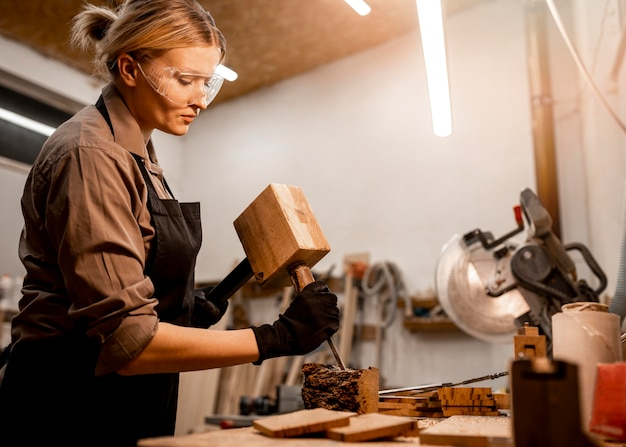 Vista laterale del falegname femminile che scolpisce il legno in studio