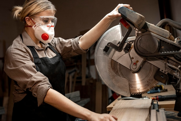 Side view of female carpenter using the round saw