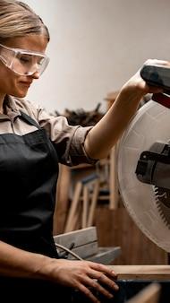 Vista laterale della donna falegname con occhiali e strumento