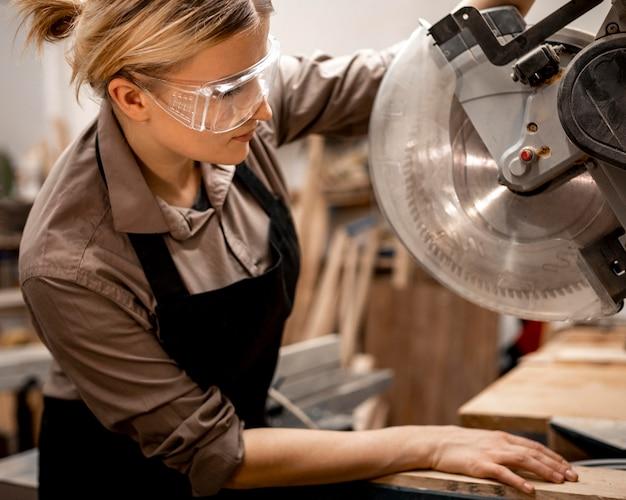 Vista laterale della donna falegname con strumento e occhiali di sicurezza