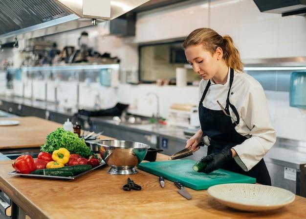 Vista laterale della donna chef in cucina per affettare le verdure