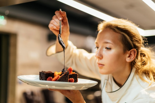 Side view of female chef pouring sauce over dish