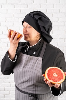 Side view of female chef smelling cut grapefruit