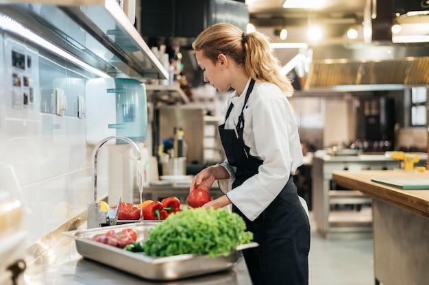 Vista laterale del cuoco unico femminile che lava le verdure in cucina