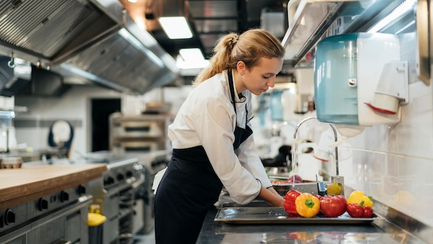 Side view of female chef washing vegetables