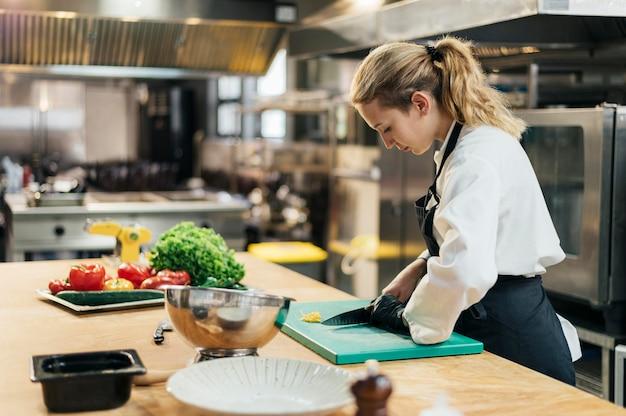 Vista laterale della donna chef con guanto per affettare le verdure in cucina