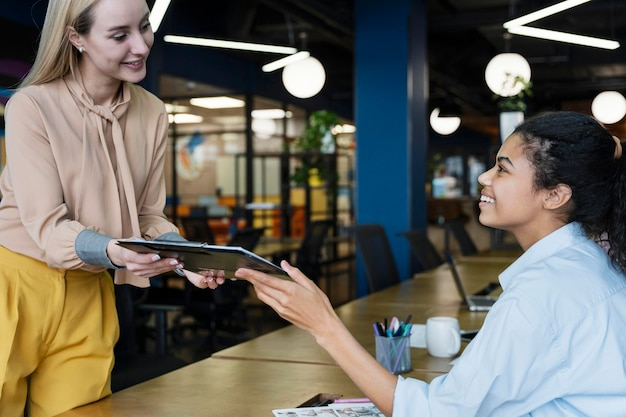 Side view of female coworkers smiling at each other and sharing documents