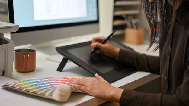 Side view of female designer working with drawing tablet and colour swatch on computer desk