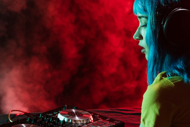 Side view female dj mixing and covered in red smoke