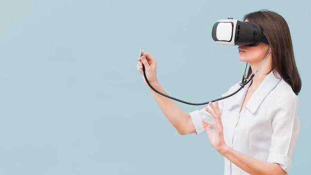 Vista laterale della dottoressa utilizzando stetoscopio e cuffie da realtà virtuale
