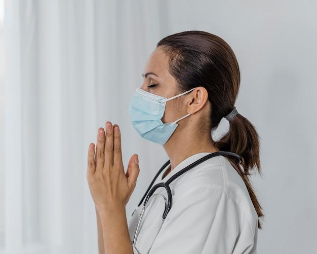 Vista laterale della dottoressa con maschera medica pregando