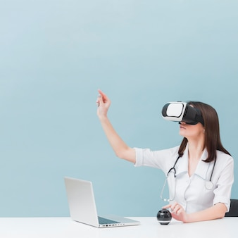 Side view of female doctor with stethoscope using virtual reality headset