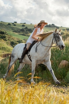 Side view of female farmer horseback riding in nature